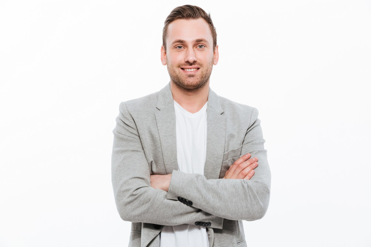 Portrait of successful man having stubble posing on camera with broad smile keeping arms folded isolated over white background